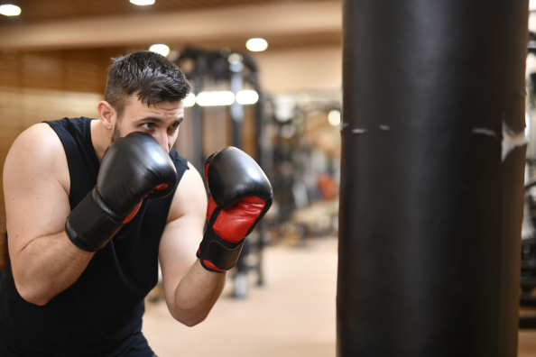 boxeador con guantes entrenando en el saco de boxeo