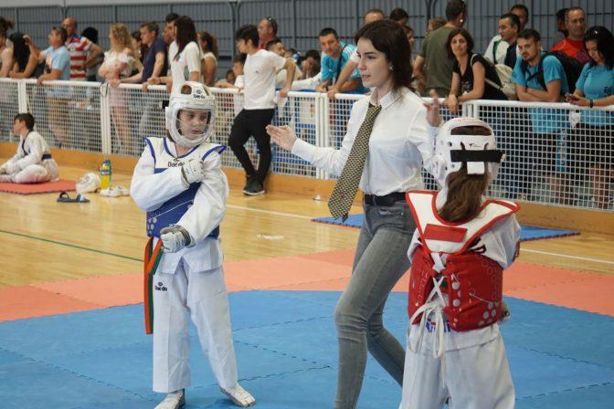 dos competidores de taekwondo combate wtf con el arbitro femenina a punto de empezar la pelea en un campeonato